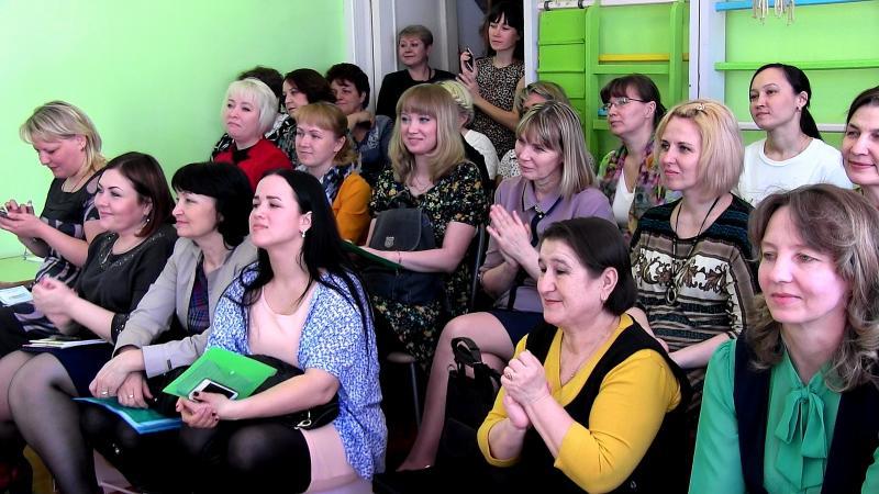 Родители сидят на собрании в комнате с зелёными стенами
