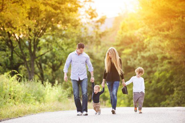 Мама, папа и два ребёнка на прогулке в парке