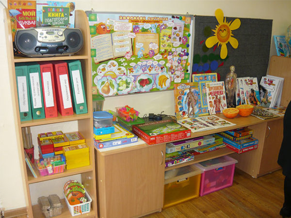 Шкаф, стол и полки, зонированные под разные центры: под столом коробки с игрушками, над столом плакат о здоровом питании