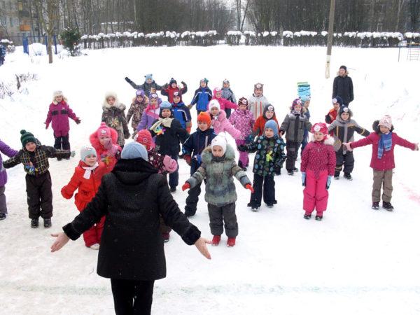 Дети в зимней одежде выполняют спортивные упражнения, воспитатель показывает