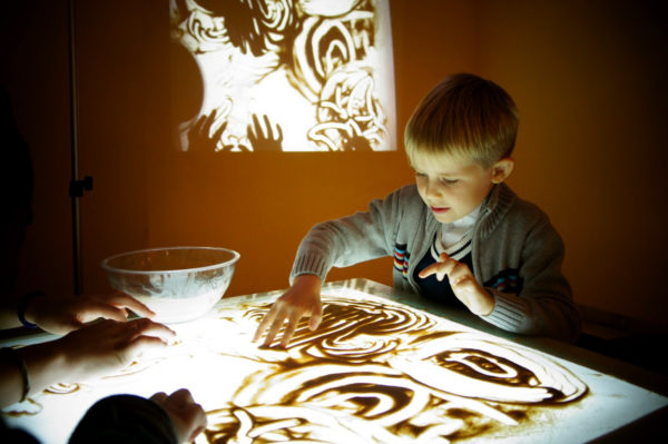 Мальчик рисует песком на специальном столе с подсветкой