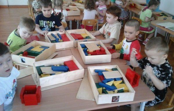 Дети сидят за столами, перед ними разложены индивидуальные строительные наборы