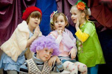 Три девочки и мальчик в сиреневом парике в актёрских образах