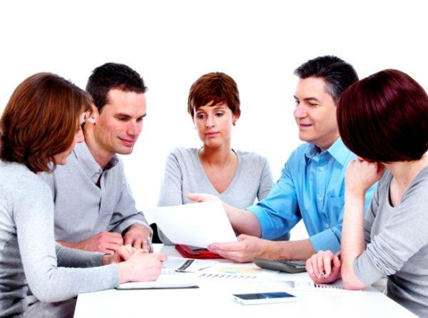 Три женщины и два мужчины сидят за столом и что-то обсуждают