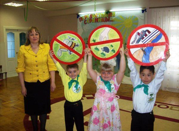 Трое детей держат запрещающие знаки по правилам поведения на природе, воспитатель стоит рядом