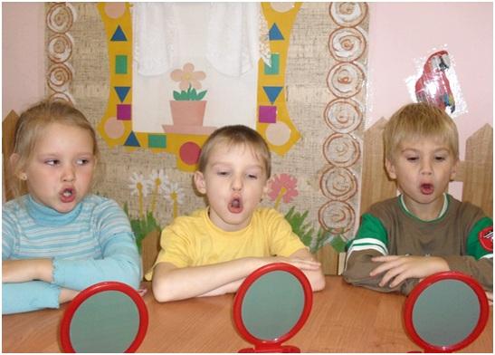 Трое детей произносят звук «О» перед зеркалами