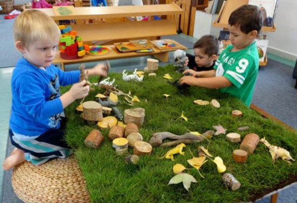 Трое детей рассматривают природный материал, находящийся на куске газона