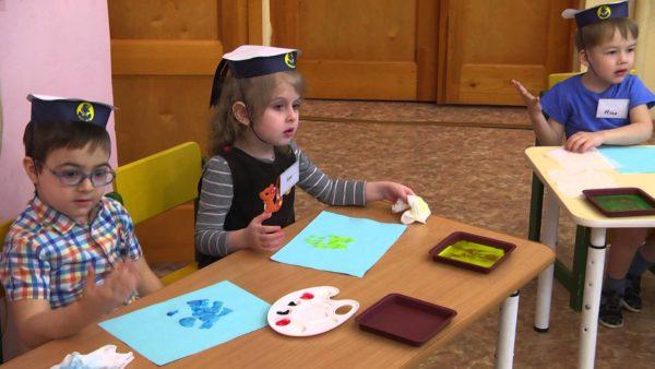Трое детей в бескозырках за столиками рисуют