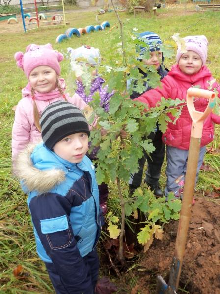 Дети в весенней одежде принимают участие в посадке дерева