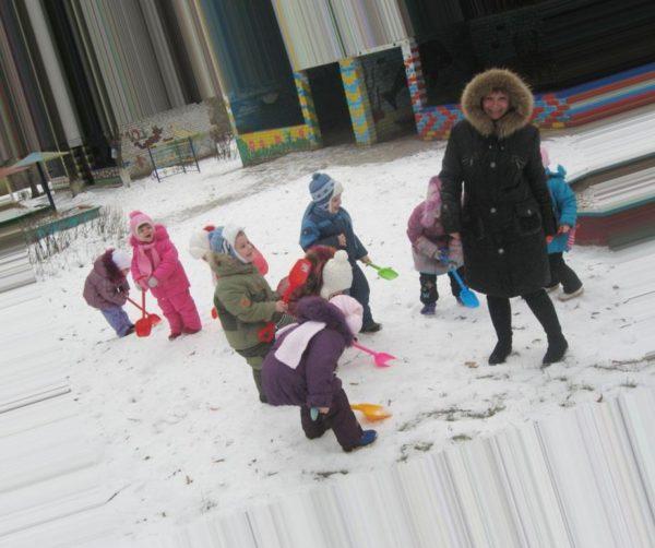 Дети во дворе с помощью лопаток убирают снег, воспитатель улыбается