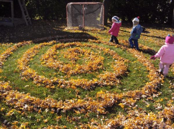 Трое детей идут по осеннему лабиринту из листьев