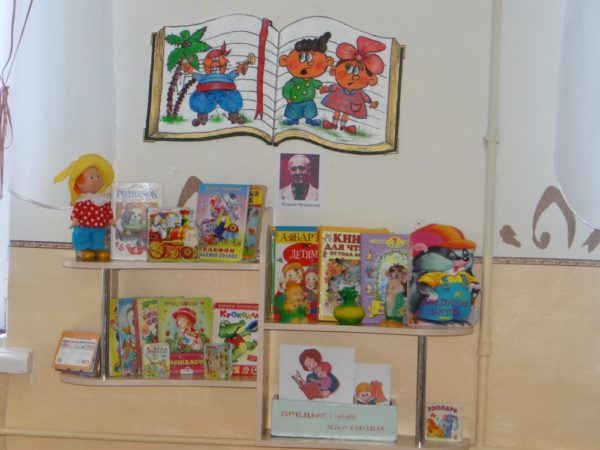 Уголок чтения в детском саду с книгами на полках и иллюстрациями на стене