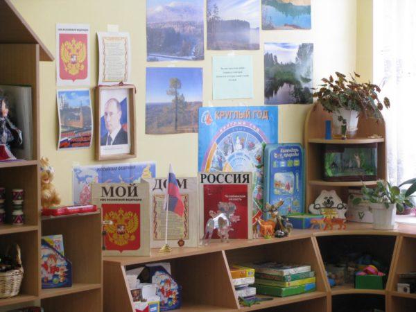 Уголок патриотического воспитания с портретом Путина, книгами Мой дом Россия, справа на картинках пейзажи