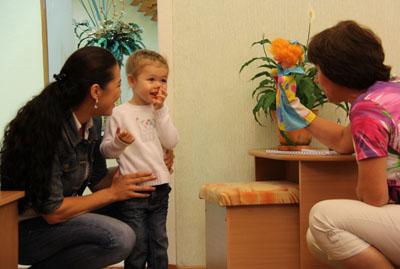 Ребёнок стоит рядом с мамой в дверях, воспитательница показывает ему куклу