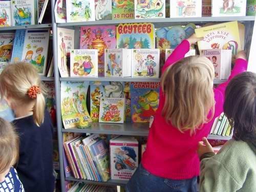 Дети рассматривают книги, стоящие на полках
