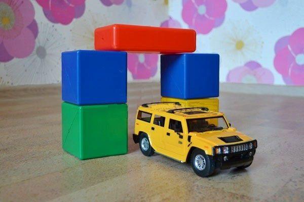 Арка из строительного конструктора и жёлтая игрушечная машина
