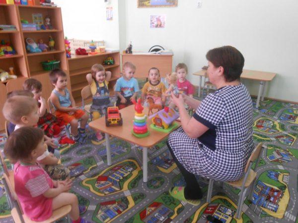 Воспитатель держит в руках куклу, дети внимательно наблюдают