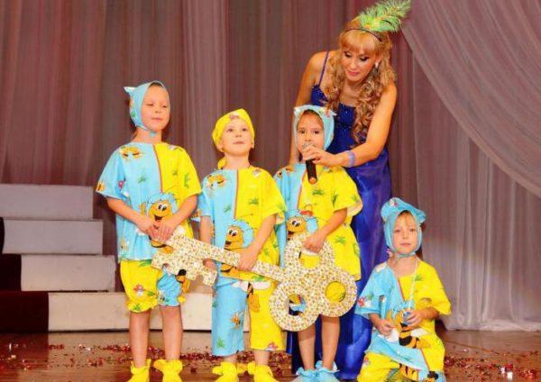 Воспитательница и четыре ребёнка в костюмах на сцене, дети держат большой ключ