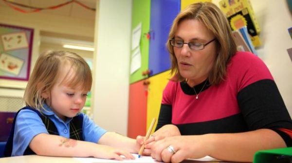 Воспитательница показывает девочке, что и где писать на листе