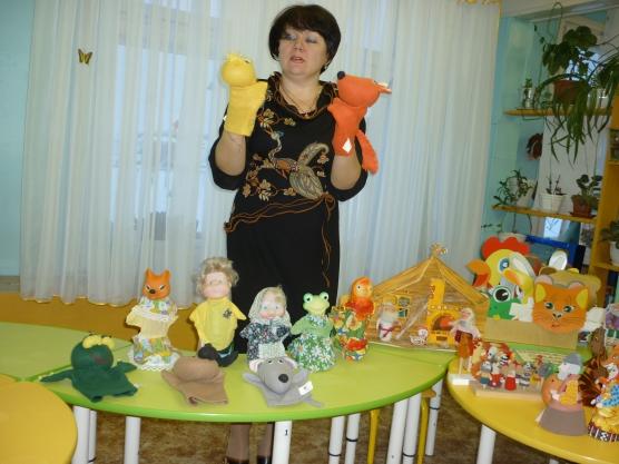 Воспитательница показывает надетые на руки куклы-перчатки