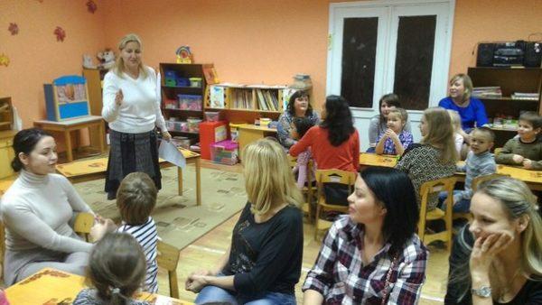 Воспитательница выступает перед сидящими по группам родителям с детьми