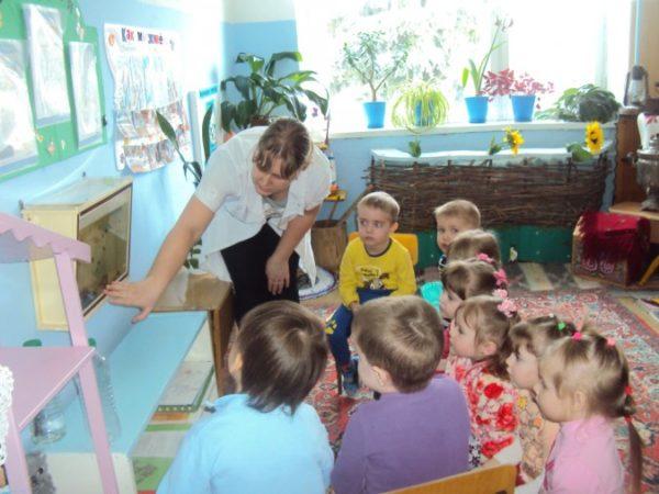 Воспитательница рассказывает о рыбах в аквариуме сидящим на стульях детям