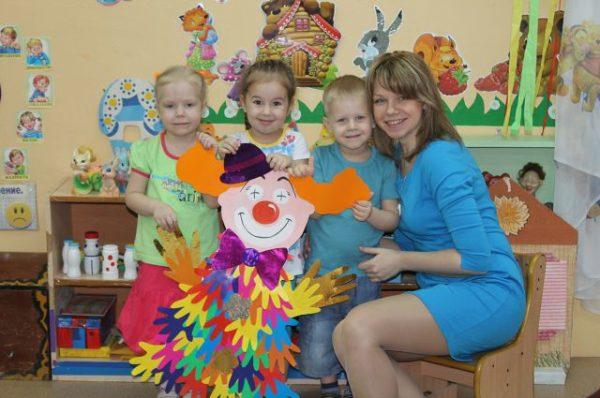 Молодая воспитательница и дети держат перед собой клоуна из бумажных детских ладошек