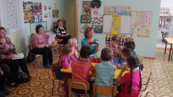 Воспитательница сидит вместе с детьми за круглым столом, взрослые сидят по периметру комнаты