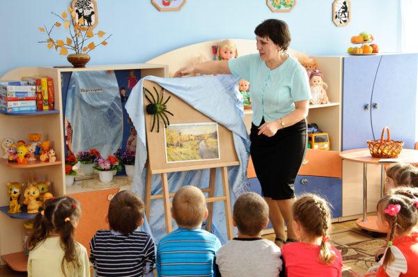Воспитательница снимает накидку с мольберта, на котором закреплён паук-игрушка, дети наблюдают