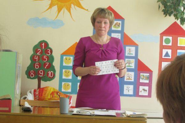 Воспитательница стоит с карточкой в руках на фоне бумажного дерева с цифрами и домиков из цветной бумаги на стене