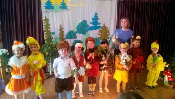 Воспитательница в окружении детей в костюмах и с цветами