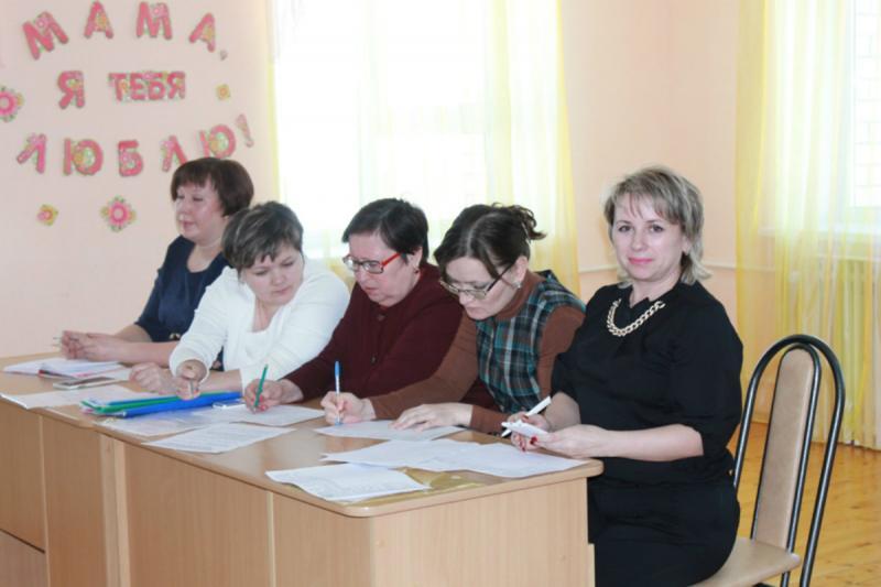 Воспитательницы впятером сидят за столом, делают пометки