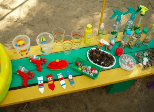 На скамейке разложены материалы для игр с водой: стаканчики, брызгалки, водяные пистолеты и др