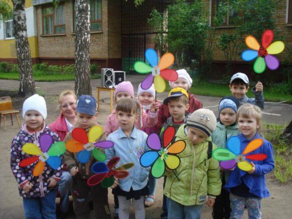 Дошкольники стоят на улице с вертушками в руках