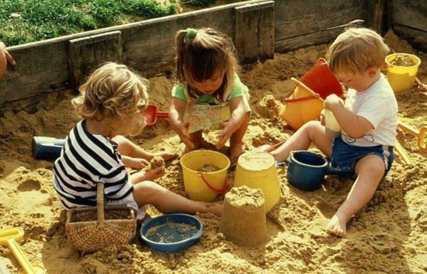 Две девочки и мальчик играют в песочнице