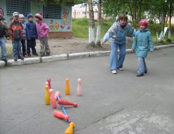 Дети и воспитатель играют на улице в кегли