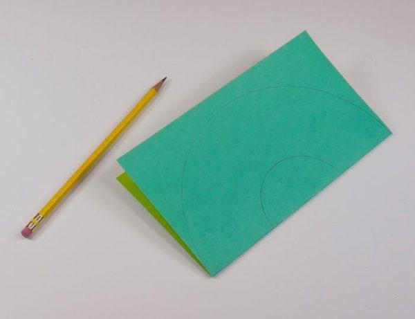 Карандаш и сложенный пополам лист бумаги с изображением кругов
