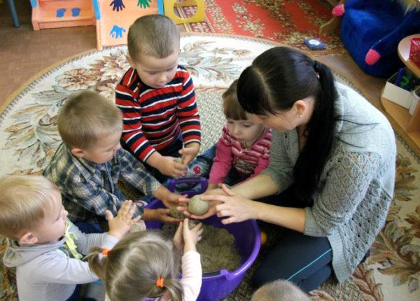 Воспитатель знакомит малышей со свойствами мокрого песка