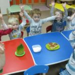 Дети сидят за столами, подняв руки вверх