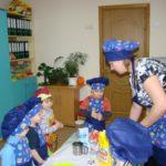 Педагог показывает детям, как замешивать тесто