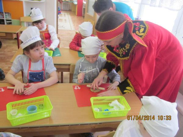 Дети сидят за партами в белых головных уборах и раскатывают тесто