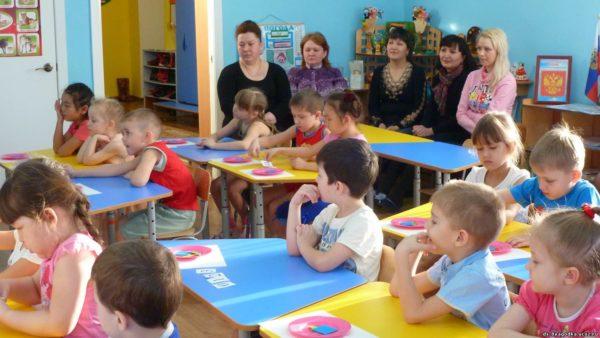 Дети сидят за партами, пятеро взрослых наблюдают