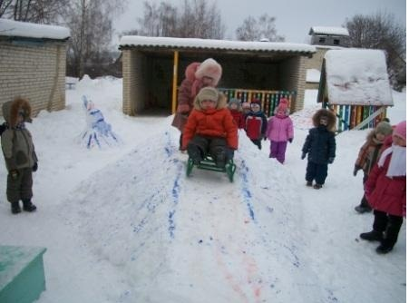 Ребёнок едет на санках по снежной горке, остальные дети наблюдают