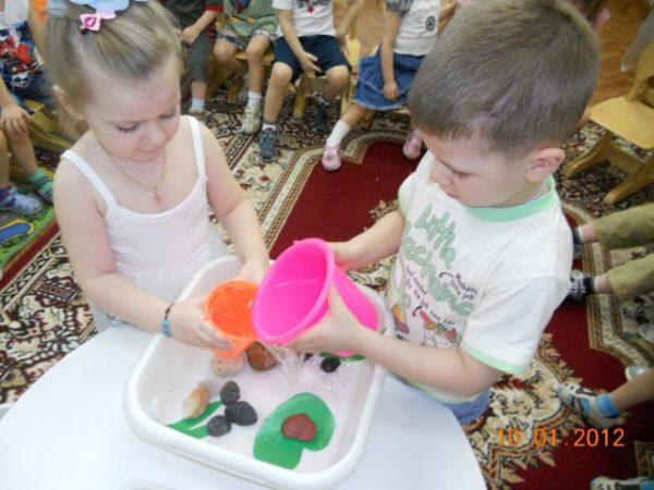Мальчик и девочка наливают в тазик воду из пластмассовых ведёрочек