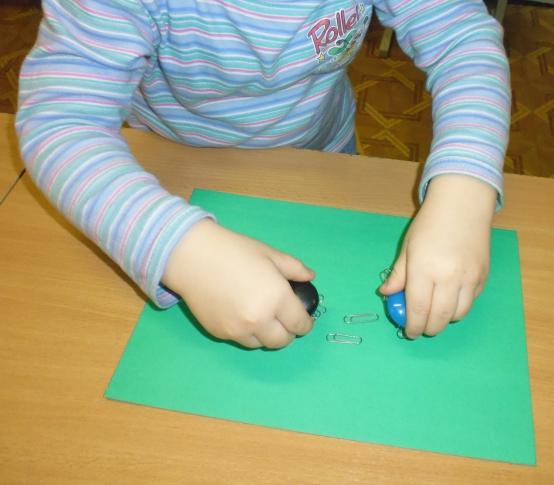 Ребёнок водит магнитами над металлическими скрепками