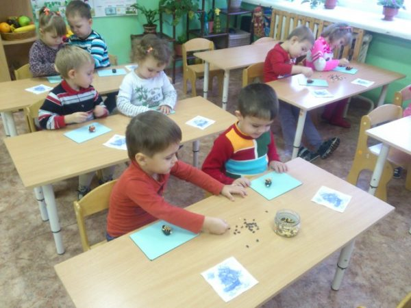 Дети 3–4 лет, сидя за столами, лепят ёжиков