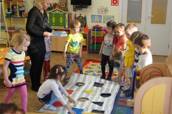 Дети и воспитатель стоят вокруг полотна с вырезанными геометрическими фигурами