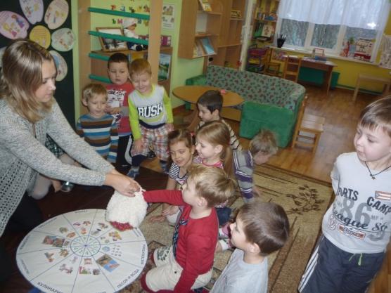 Дети берут фишки из мешочка, который держит воспитательница