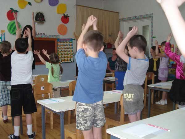 Дети стоят, подняв руки над головой