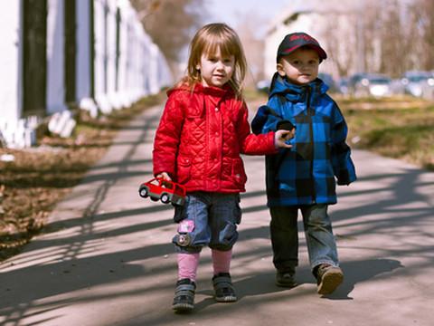 Мальчик и девочка в осенней одежде гуляют по улице